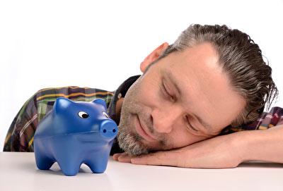 Anleger schläft vor dem Sparschwein